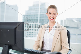 Cheerful pretty businesswoman sitting on swivel chair