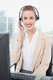 Cheerful pretty agent wearing headset dealing with customer