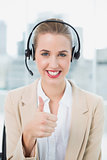 Smiling pretty call centre agent wearing headset giving thumbs up