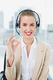 Smiling pretty call centre agent giving okay gesture