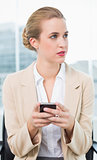 Pensive attractive businesswoman text messaging