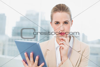 Serious attractive businesswoman using her tablet