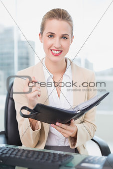 Smiling attractive businesswoman writing on her agenda