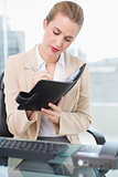 Focused attractive businesswoman writing on her agenda