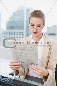 Serious businesswoman reading newspaper