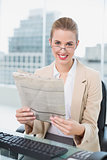 Smiling businesswoman with glasses reading newspaper