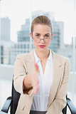 Serious businesswoman with glasses presenting her hand