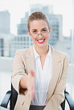 Smiling businesswoman with glasses presenting her hand