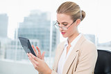 Serious businesswoman with glasses using calculator