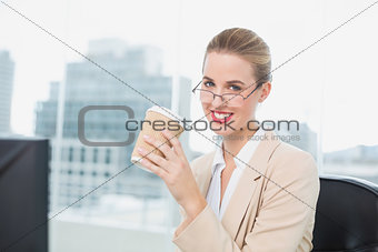 Cheerful businesswoman with glasses holding coffee