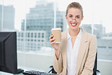 Smiling businesswoman with glasses holding coffee