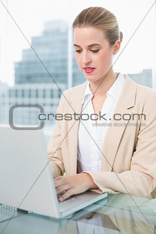 Serious businesswoman working on her laptop