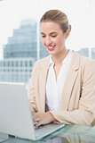 Smiling businesswoman working on her laptop