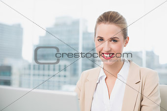 Smiling gorgeous businesswoman working on her laptop