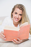 Smiling gorgeous model lying on cosy bed reading book