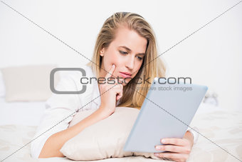 Focused pretty model using her tablet lying on cosy bed