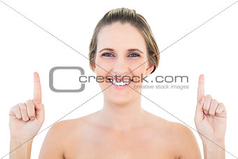 Smiling blonde woman pointing up
