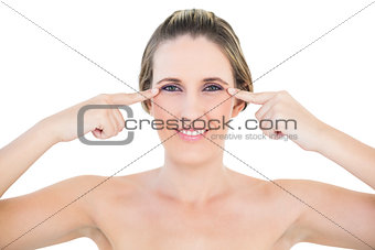 Woman smiling at camera pointing at wrinkle on her eyes
