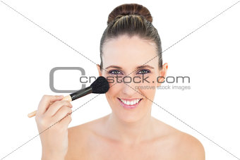 Portrait of delighted woman using blusher brush