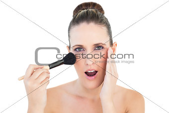 Portrait of surprised woman applying blusher
