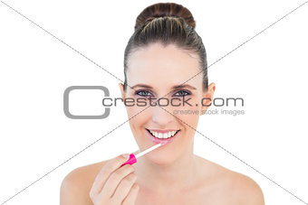 Smiling attractive woman applying lip gloss