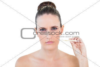 Young woman holding thermometer looking worried at camera