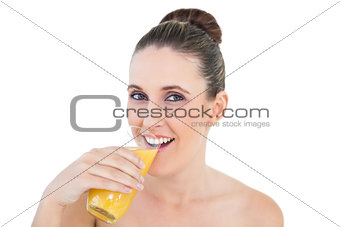Woman drinking orange juice looking at camera
