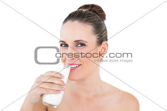 Happy woman drinking milk and looking at camera