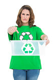 Serious woman holding and pointing at empty recycling bin