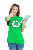 Happy environmental activist giving thumbs up holding tablet
