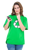 Thoughtful environmental activist holding phone looking at camera
