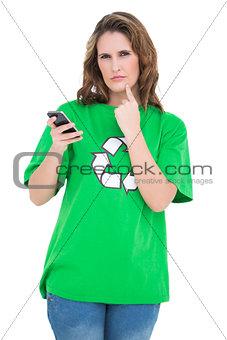 Thoughtful environmental activist holding phone looking at camera
