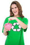 Environmental activist pointing at piggy bank
