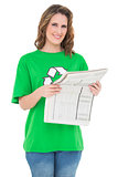 Smiling environmental activist holding newspaper