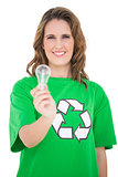 Smiling environmental activist holding light bulb looking at camera