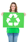 Smiling environmental activist holding recycling sign
