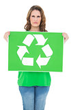 Unsmiling environmental activist holding recycling sign