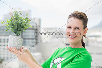 Smiling activist holding plant