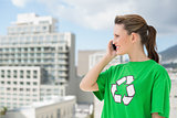 Woman wearing green recycling tshirt talking on the phone