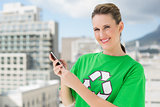 Smiling woman wearing green recycling tshirt text messaging