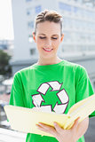 Woman wearing tshirt with recycling symbol holding notebook