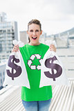 Cheerful woman in green recyling tshirt showing money bags