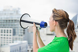 Side view of woman using megaphone