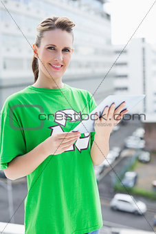 Smiling woman wearing recycling tshirt holding tablet