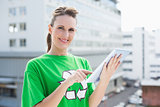 Cheerful woman wearing recycling tshirt using tablet