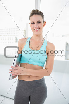 Smiling sporty woman standing holding laptop