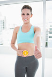 Smiling woman in sportswear holding orange slice on her belly