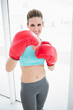 Fit woman wearing red boxing gloves