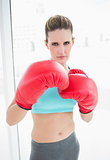 Serious woman wearing red boxing gloves