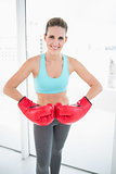 Competitive woman wearing red boxing gloves